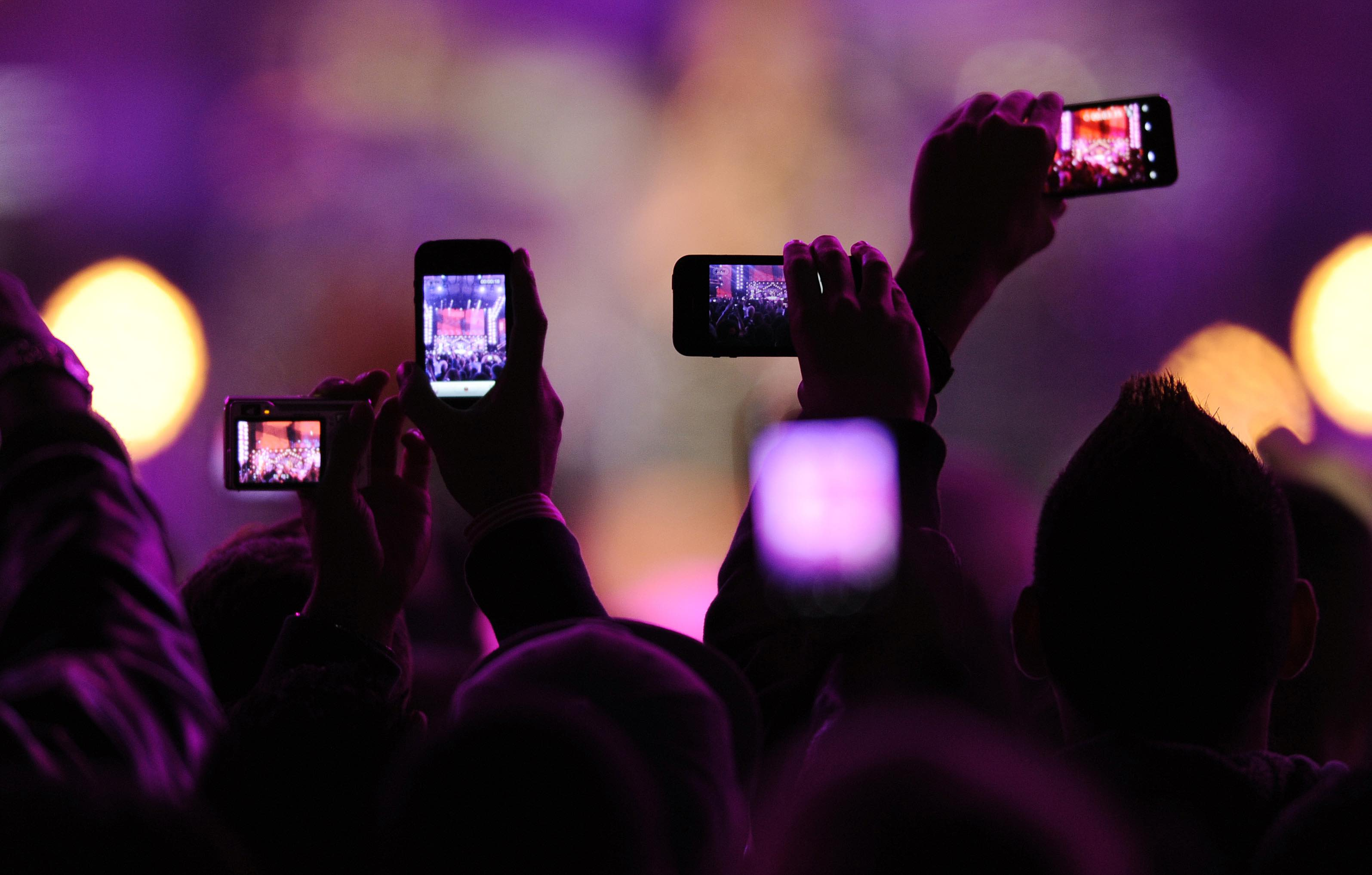 """Fans take photos with their mobile phones during the VH1 """"Divas Salute The Troops"""" show at the Marine Corps Air Station Miramar in San Diego, December 3, 2010. REUTERS/K.C. Alfred (UNITED STATES - Tags: ENTERTAINMENT SCI TECH IMAGES OF THE DAY) - RTXVDL9"""